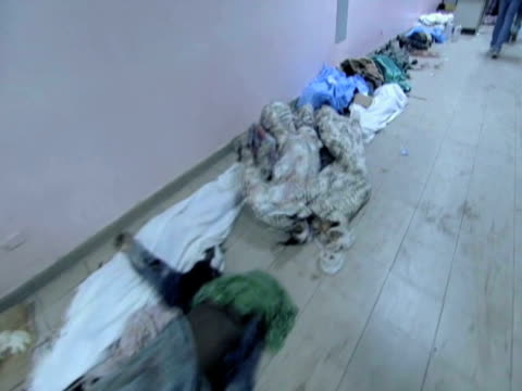 track over injured people lay on floor of hospital grounds alongside covered corpses as they wait for treatment following devastating earthquake... - hispaniola stock videos & royalty-free footage