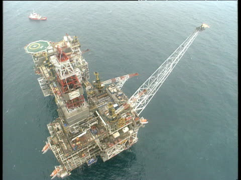 Track over large oil rig and platform with helipad and crane in North Sea