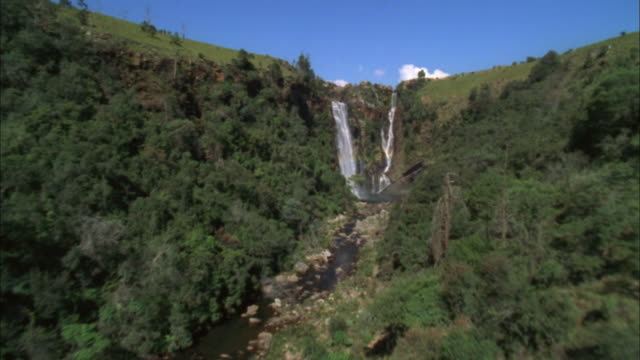 track over lush green riverbank towards waterfall, blyde river canyon available in hd. - blyde river canyon stock videos and b-roll footage