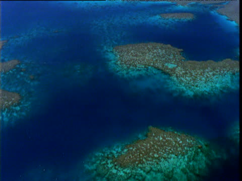Track over mottled turquoise tropical reef and shallow sea, Great Barrier Reef, Queensland, Australia