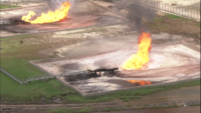 track over niger delta at port harcourt and gas burn-off at oilfield, nigeria - nigeria stock videos and b-roll footage