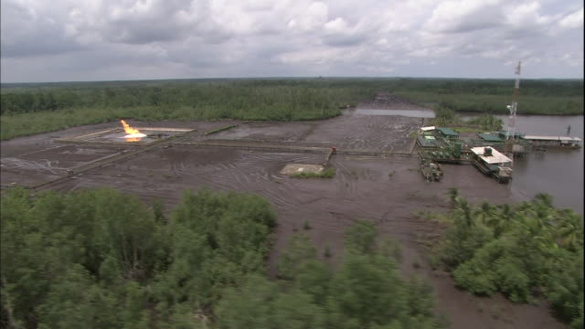 track over niger delta at port harcourt and zoom in to gas burn-off at oilfield, nigeria, aerial shot - nigeria stock videos and b-roll footage