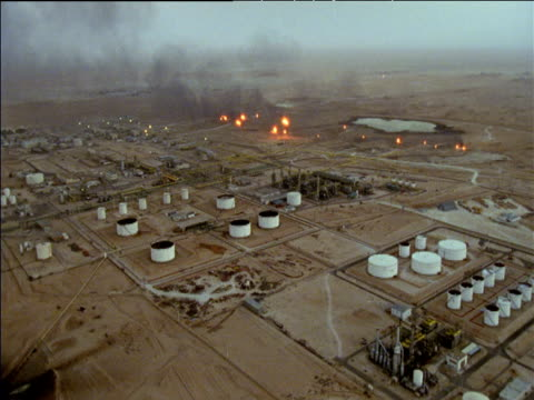 Track over oil and natural gas fields with flames burning in distance Sahara Desert