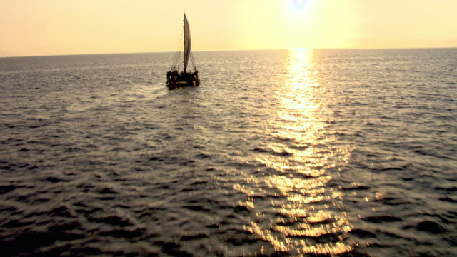 vidéos et rushes de track over polynesian canoe sailing on pacific ocean at sunset, hawaii - océan pacifique sud