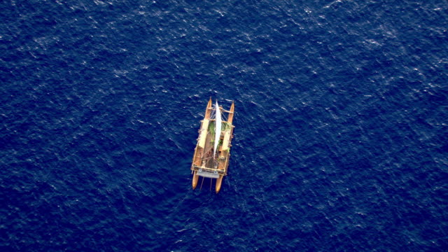 Track over Polynesian canoe sailing on Pacific ocean, Hawaii