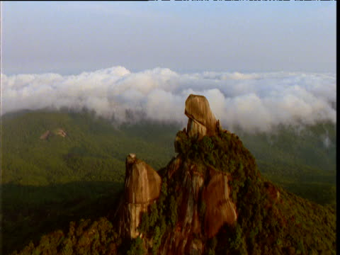 vidéos et rushes de track over rocky pillar and outcrop amongst forested hills, queensland, australia - outcrop