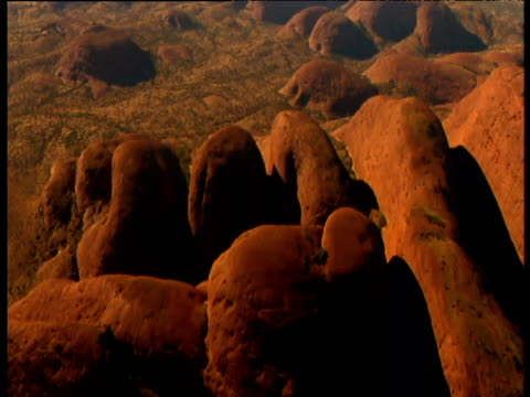 Track over rounded sandstone Olgas rising out of outback, Northern Territory, Australia