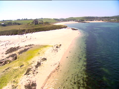 track over sandy beach surrounded by green hills. sunlight shimmers on clear waters exposing seaweed below surface. isle of scilly. - isles of scilly stock videos & royalty-free footage
