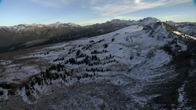 vídeos de stock, filmes e b-roll de track over snow covered rocky hills, yellowstone, usa - terreno extremo