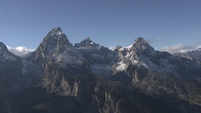 vídeos de stock, filmes e b-roll de track over snowy mountain peaks, yellowstone, usa - terreno extremo