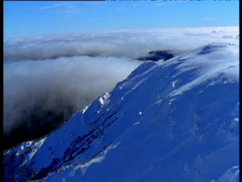 track over snowy peak revealing cloud below in australian alps, victoria, australia - australian alps stock videos & royalty-free footage