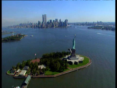 vídeos de stock e filmes b-roll de track over statue of liberty manhattan island in the background tilt up to reveal helicopter rotors includes the world trade center. - world trade center manhattan