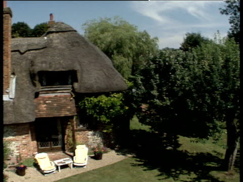 track over thatched cottage with neat garden and swimming pool to brown fields crawley hampshire - hampshire england stock videos & royalty-free footage