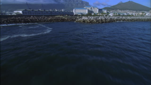 Track over Victoria and Alfred waterfront development and ships in harbour with Table Mountain in background, Cape Town Available in HD.