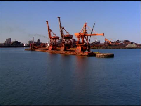 stockvideo's en b-roll-footage met track over water to cranes and factories on docks, baltimore - verwerkingsfabriek