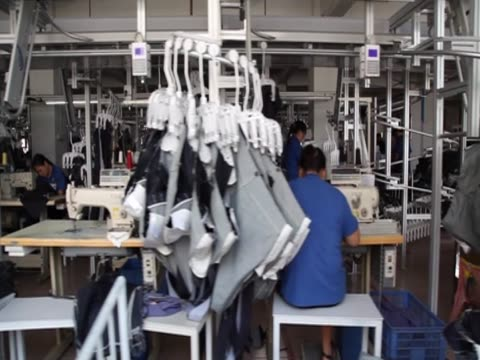 stockvideo's en b-roll-footage met track over women working in a denim factory in xintang southern china - spijkerstof