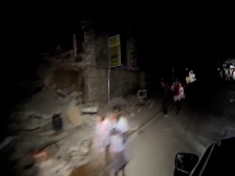 vídeos de stock e filmes b-roll de track past destroyed houses and people walking along streets at night following devastating earthquake haiti 14 january 2010 - hispaniola