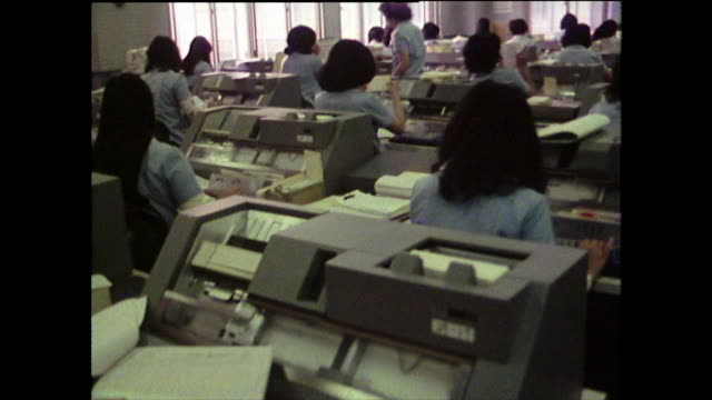 track past female office workers on punch card machines; 1975 - bbc archive stock-videos und b-roll-filmmaterial