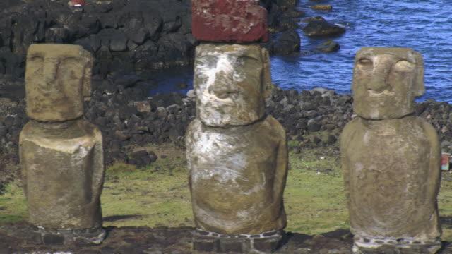 track past moai statues on ahu platform on rocky coast, easter island - maui stock videos & royalty-free footage
