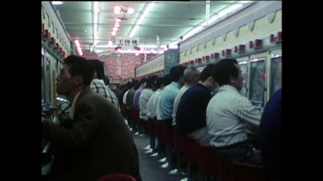 track past open pachinko parlour full of players; 1975 - bbc archive stock-videos und b-roll-filmmaterial