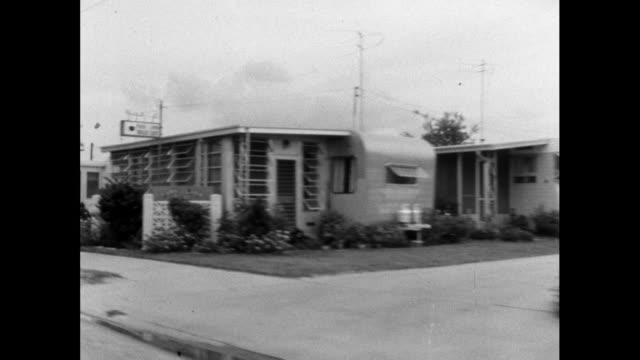 stockvideo's en b-roll-footage met track past residential trailer park in usa; 1964 - establishing shot