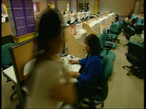stockvideo's en b-roll-footage met track past rows of desks and operators in a call centre india 2003 - uitbesteding