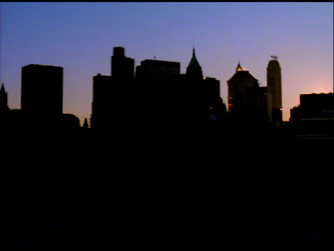 Track past silhouetted skyline of New York to star burst filter effect on setting sun, Manhattan