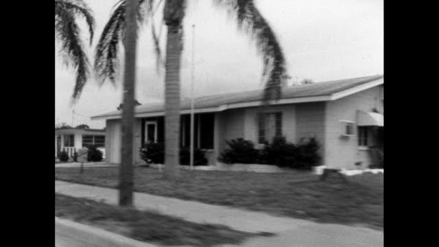 stockvideo's en b-roll-footage met track past single storey residential housing in usa; 1964 - establishing shot