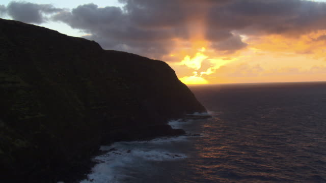 track past tall cliffs and sea at sunset, easter island - klippe stock-videos und b-roll-filmmaterial