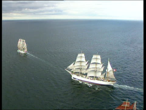 track past tall ships under full sail at sea including schooner three masted and four masted barques and a smaller brigantine england - schiffsmast stock-videos und b-roll-filmmaterial