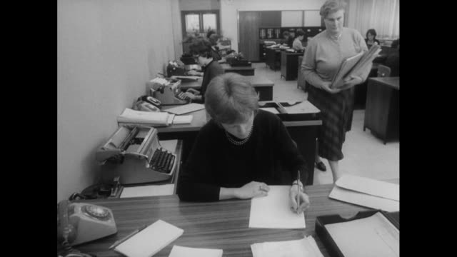 track past woman working at an office desk; 1963 - office stock videos & royalty-free footage