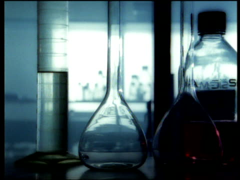 Track right along laboratory shelf holding glass flasks, beakers and jars, silhouettes of chemists in background