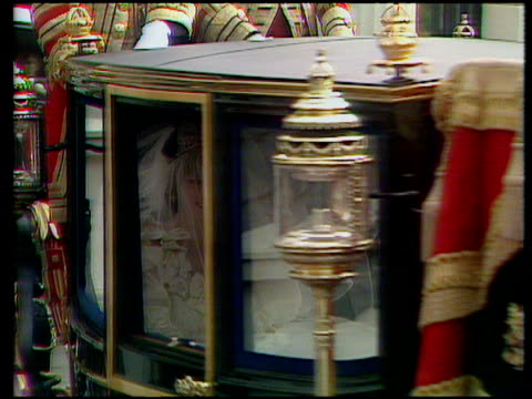 track right and zoom in as horse drawn carriage leaves clarence house with lady diana and earl spencer inside wedding dress partly visible through... - cocchio video stock e b–roll