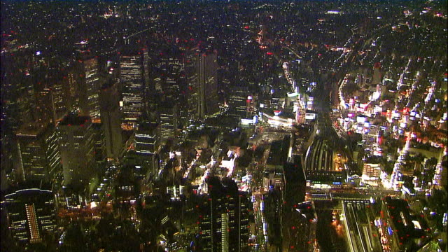 Track right and zoom into neon signs, high rise buildings and streets of Shinjuku