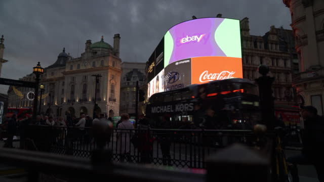 track right as traffic and pedestrians pass in front of the bright lights of piccadilly circus, london - piccadilly circus stock videos and b-roll footage