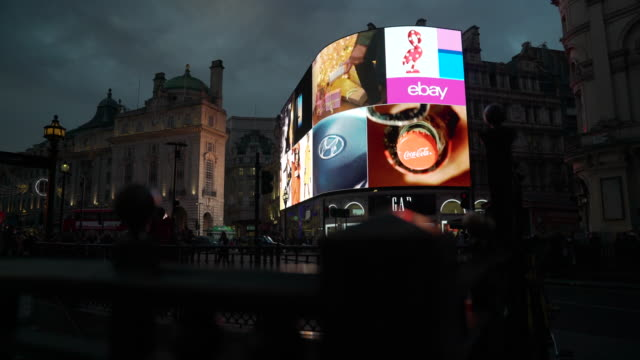 track right as traffic and pedestrians pass in front of the bright lights of piccadilly circus, london - video wall stock videos & royalty-free footage