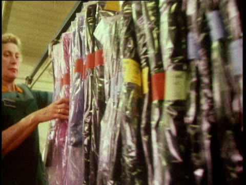 track right as woman guides rail of dresses ready for transporting from clothing factory london; 1970's - production line worker stock videos & royalty-free footage