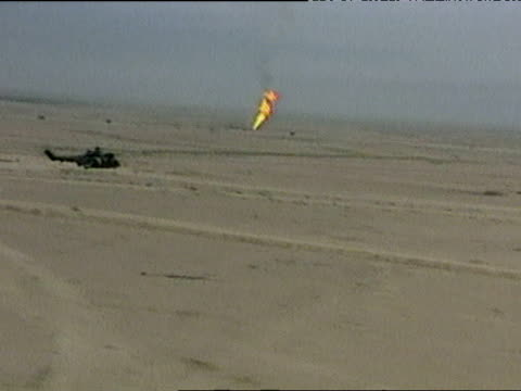 track right following helicopter as it flies past oil fire burning in desert during iraq war 24 mar 03 - iraq stock videos and b-roll footage