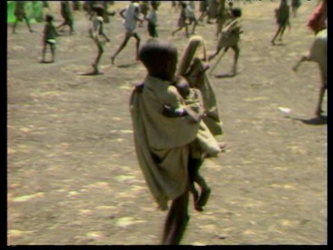 vídeos y material grabado en eventos de stock de track right following young boy carrying baby during ethiopian famine oct 84 - etiopía
