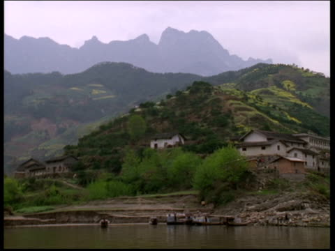 Track right from boat along Yangtze River Chinese style houses among lush green hills China