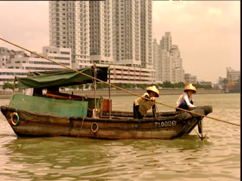 vidéos et rushes de track right from boat past two people in straw coolie hats on small moored boats hong kong - chapeau de paille