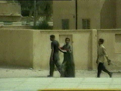 track right from vehicle past iraqis waving iraqi flag during iraq war 24 mar 03 - iraq war stock videos and b-roll footage