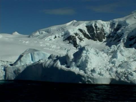 wa track right, iceberg floating past mountainous coastline of paradise bay area, antarctic peninsula - antarctic peninsula stock videos & royalty-free footage