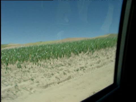 track right in 4x4 across barren mountainous landscape past poppy fields afghanistan - eskapismus stock-videos und b-roll-filmmaterial