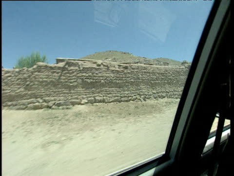 Track right in 4x4 past stone wall of remote town Afghanistan
