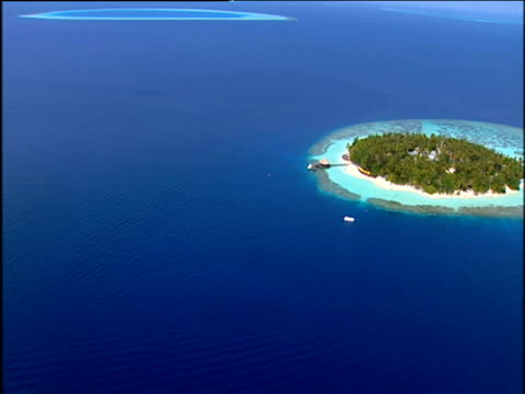 track right over circular tropical island surrounded by white beaches turquoise shallows and dark blue seas maldives - maldives stock videos & royalty-free footage