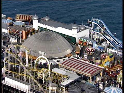 track right over fairground rides on palace pier brighton - ブライトン パレスピア点の映像素材/bロール