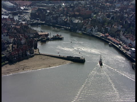 track right over replica hms endeavour as it sails up river esk estuary tilt up to town docks whitby yorkshire - british military stock videos & royalty-free footage