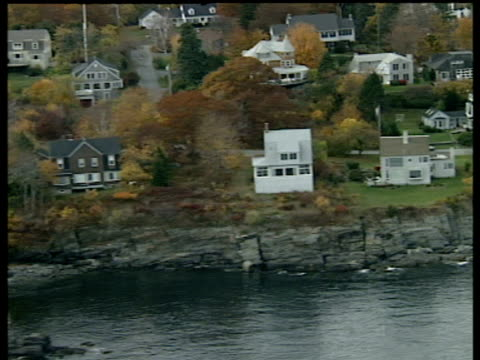 Track right over residential housing surrounded by autumn trees on rocky coast Maine