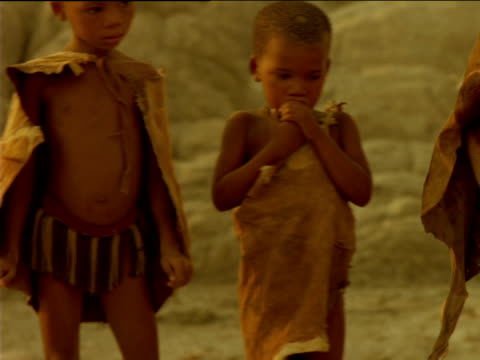 track right past group of basarwa children as elder tribeswoman crouches down to tend to campfire, botswana - giovane nell'animo video stock e b–roll